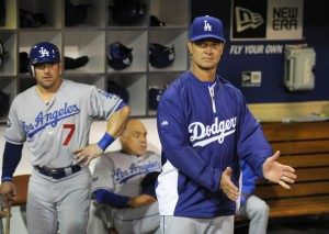 Dodgers manager Don Mattingly cheers on his team while Nick Punto waits for his next at-bat.