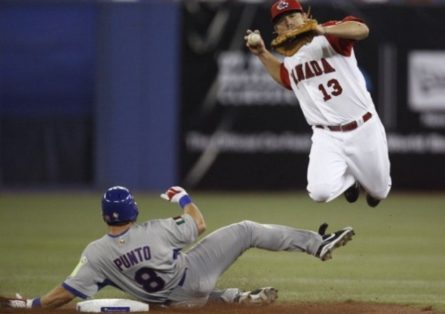 Team Italy's Nick Punto slides hard into second base to break up a double play against Team Canada in the 2013 World Baseball Classic in Phoenix, Arizona.