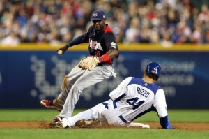 Anthony Rizzo slides into Team USA's Brandon Phillips to break up a double play attempt.