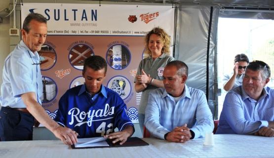 Italian MLB Academy Director Bill Holmberg (far right) smiles as Kansas City Royals prospect Marten Gasparini signs his professional baseball contract.
