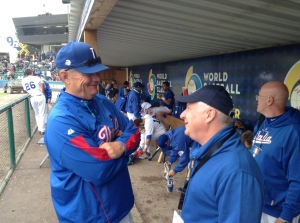 Team Italia pitching coach Bill Holmberg visits with Roberto Angotti in the dugout (Photo courtesy of IandI-GoPro.com).