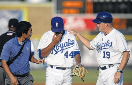 2014 Burlington Royals shortstop Marten Gasparini, center, is tended to by trainer Saburo Hagihara and manager Tommy Shields after he was struck in the face by a thrown ball which nearly broke his nose.